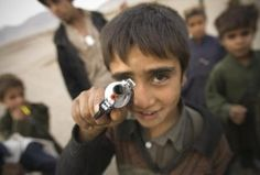 An Afghan boy aims a toy gun at camera as he stands in a village near Herat, Afghanistan October 29, 2009.  REUTERS/Morteza Nikoubazl Syrian Children, Boys Playing, Alone, Afghanistan, Places To Go, City, October 29, People, Gun