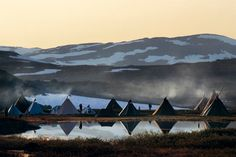 Traditional tents beside the reindeer-branding enclosure in a Sami village.