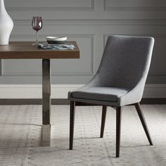 Pull up modern style to any table in your home with this chic and sophisticated side chair. Brimming with midcentury-inspired appeal, this piece will give your room an updated and elegant look. The slim espresso-finished legs give this chair a crisp look and they elegantly contrast the cool gray fabric on the seat. With a neutral color palette, this piece can blend in with a variety of settings while still adding a pop of distinctive style. Try surrounding an espresso-finished table with six…