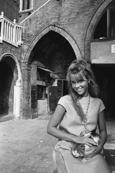 """janefondadaily: """"Jane Fonda photographed by Philippe Le Tellier, posing with a cat in the courtyard of Campiello del Remer, at the Venice film festival (1966)"""