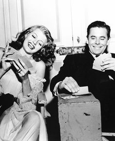 Rita Hayworth and Glenn Ford playing cards between takes on the set of Gilda.