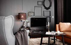 Una forma de disimular el televisor es pintar la pared de detrás de color negro y decorar con marcos negros el resto del espacio para acabar de definir el estilo
