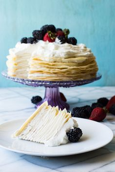 A whipped lemon mascarpone cream filling is layered with lightly sweetened crepes for a perfect dessert or brunch recipe!! Topped with lemon curd whipped cream and fresh berries!