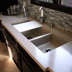 Counters with undermount concrete sink and sliding cutting board.