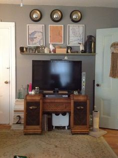 """DIY mantle and tv wall. 3 convex mirrors, old maps and a DIY mantle (old wood from the attic plus two brackets ive had lying around, $0!) frame his TV (he HAD to have something that big in this teeny house!). Old vanity from my attic, again, $0, stacks of books directly on the floor hide the tv """"guts"""" hanging down."""