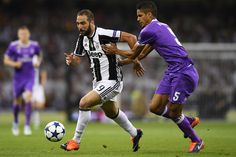 Gonzalo Higuain of Juventus and Raphael Varane of Real Madrid battle for possession during the UEFA Champions League Final between Juventus and Real Madrid at National Stadium of Wales on June 3, 2017 in Cardiff, Wales.