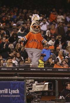 San Francisco Giants mascot Lou Seal in a baby giraffe hat for first baseman Brandon Belt during the ninth inning against the Baltimore Orioles at AT