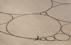 Jim Denevan etches impermanent geometric drawings into California beaches. His geometric sand sculptures are made with little more than rakes and sticks and can span miles of North California beaches.