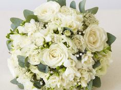 A wintry palette is created in this elegant bouquet by using white 'Avalanche' roses,  white freesias, white trachelium and eucalyptus stems.