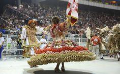 Porta-bandeira e Mestre-sala desfilam com roupas ricas em detalhes em vermelho e dourado, 2013.