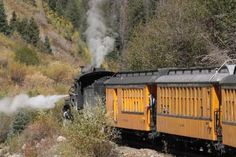The bright yellow vintage passenger cars add color to photographs along the Animas River.