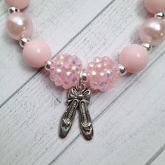 Ballerina Ballet Slippers charm bracelet. It is a 6.25 inch bracelet on stretchy cord with round pink acrylic pearl like beads, opaque pink beads, pink rhinestone beads and a silver tone ballet slippers charm. Perfect for a party favor or a Recital gift for her ballerina friends. As pictured above, I have other Ballerina designs available. Bracelets are recommended for girls 3 years and up. You are purchasing 8 completely assembled 6.25 bracelets - 8 Party Favors If you need additional…