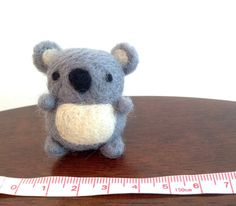 Go down under by adding this charming needle felted koala magnet to your fridge. The koala is handmade with love out of 100% natural wool. This miniature koala friend would make a perfect gift for an animal lover or anyone who enjoys cute things.  Measurements are approximately:  3.5cm w x 4.0cm h (1.4w x 1.5h)  As this item is made to order, it may vary slightly from the photos shown. Each is handmade and one-of-a-kind.  Item will be carefully packaged using recyclable materials.  Not…