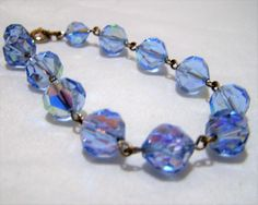 Mid Century beaded bracelet Faceted blue glass beads with aurora borealis coating, linked together by silver tone metal links C spring clasp 7 1/4 inches long by 3/8 inch wide Good vintage condition  International buyers welcome, over charges are refunded Priority shipping is optional 11117  Want to see more great bracelets? Click here: https://www.etsy.com/your/shops/GretelsTreasures/sections/14162689  Credit cards and paypal welcome..