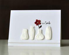 CAS. Clay embellished vases on a shelf.