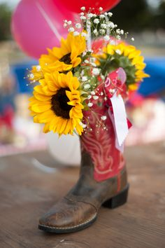 Cowboy boots and sunflowers centerpiece at a Cowgirl Birthday Party! See more party ideas at CatchMyParty.com!