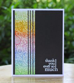 handmade card from What's Next? ... black panel ... colorful band of emboss resist technique with background stamp cut into long strips ... like it!