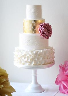 Lovely brushed gold, and frilly bottom tier between other white textures. The splash of color from the flower is very beautiful.