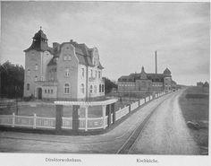 Schwarz-Weiß-Foto: Straße mit zwei Häusern auf der linken Seite und Bäumen und großen Schornstein im Hintergrund