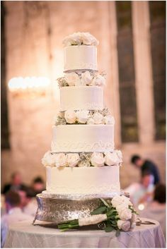Tall four tiered white wedding cake with ivory roses | Rachael Hall Photography | www.theknot.com