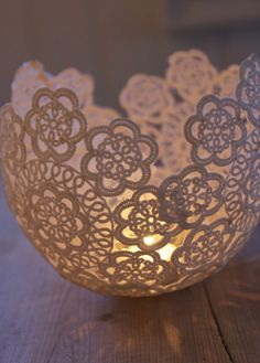 Hang a blown up balloon from a string. Dip lace doilies in wallpaper glue and wrap them on a balloon. Once they're dry, pop the balloon and place a tea light candle inside.