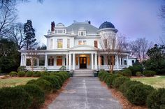 This textile Magnate's grand southern mansion has a formal entry, wrap around porch, windows peak, white railing along the roof and a domed tower.