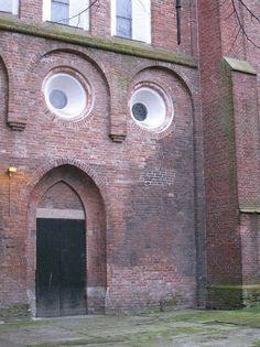 視線を下げる人(レンガ造りの家)