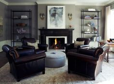 Furniture arrangement. (Everyone gets their own chair)  Dark painted fireplace surround.