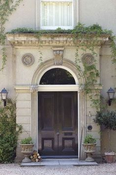Gorgeous arched stone front door detail - like the contrast of the light stone and dark door