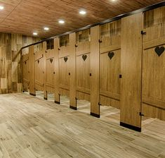 Outhouse custom toilet partitions by Ironwood Manufacturing. Laminated slat construction with engraved hearts. Floor mounted.