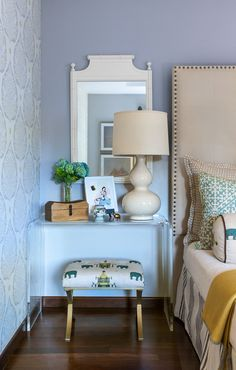 Lamp-A serene bedside vignette incorporates a thrifted mirror, a bench from Target that was reupholstered in designer fabric, affordable, original art and the homeowner's keepsakes.