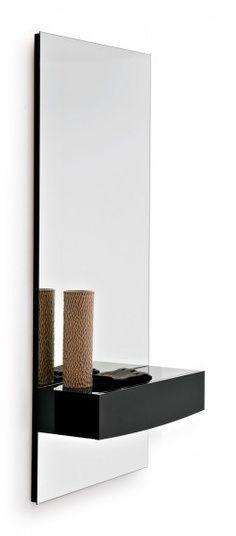 En la pared està un espejo basico cuadrado con un estante negro de madera.