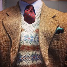 Tan tweed jacket, light blue shirt, red tie, beige fair isle sweater