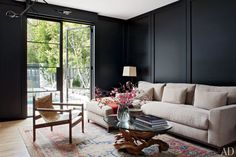 In the study, a midcentury armchair from Blackman Cruz is grouped with a vintage glass-top driftwood table and a custom-made sectional by Molly Isaksen Interiors upholstered in a Wyeth linen.