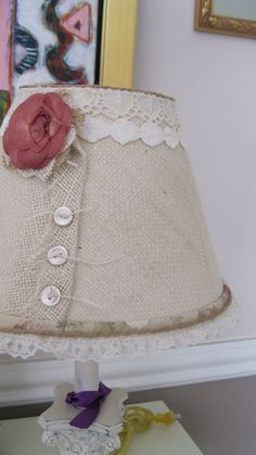 Sweet lamp shade done in burlap, fabric, buttons and a rose. Would look great really anywhere.  Lamp shade measures 5 T x 10 B x 7 H Shade is a clip on.