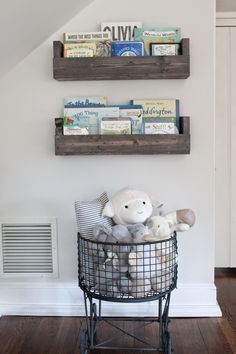 How cute is this little nook in the nursery. Pretty wood shelves with a basket full of stuffed animals..nothing better.