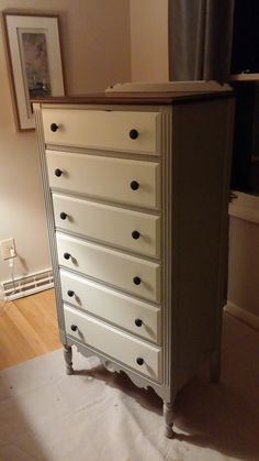 Tall chest painted in soft gray and sandcastle white.  I also restained the top and replaced the wood knobs.
