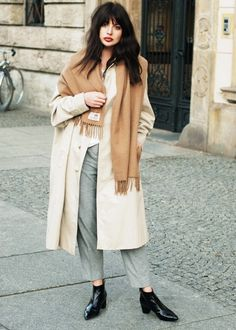 Laura Matuszczyk of Horkruks wears a neutral coat, tan scarf, gray trousers, and black ankle boots