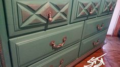 Turquoise dresser with silver metallic trim.