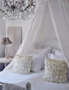 love ruffled pillows and chandelier above bed!