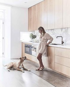 Kitchen: Louisa with her dog Sim. The polished concrete floor was part of the original house and fits in with the updates, and the original spotted gum flooring was sanded, limewashed and revived by Mint Floor Sanding & Finishing. Modern Kitchen Renovation, Home Renovation, Kitchen Remodelling, Kitchen Benchtops, Kitchen Flooring, Kitchen Splashback Ideas, Kitchen Cabinetry, Kitchen Countertops, Spotted Gum Flooring