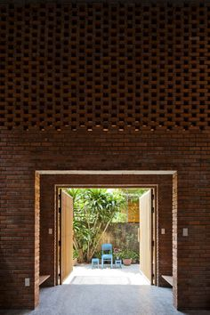 Portals opening out to a simple outdoor landscaped area Termitary House / Tropical Space