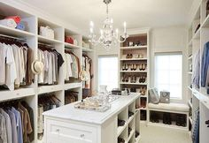 Traditional white walk in closet boasts a George II Chandelier hung over a marble top island fitted with shoe shelves and glass cabinet pulls.