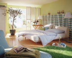 Schlafzimmer in Ferienhaus-Optik Weiße Klappläden, weiß-blau gestreifter Stoff, sandfarbenes Parkett - dieses Schlafzimmer weckt mit seiner Farbkombination zu jeder Jahreszeit Sommergefühle. Das weiche Lindgrün der Wand entspannt den Blick, und der saftig grüne Teppich wirkt fast wie ein kleines Stück Rasenfläche. In solch einer Umgebung lässt es sich auf der hellblauen Récamiere ganz relaxed ausruhen.