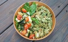 Pesto pasta with roasted zucchini, cherry tomatoes, onions, and banana peppers all from the garden on a bed of spinach