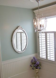 Another view of window trim, wainscoting, plantation shutters and chandelier.