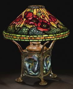 "TIFFANY STUDIOS ""POPPY"" TABLE LAMP with a rare ""Turtleback Tile"" base, the shade with a rare patinated bronze decorative rim collar oil canister impressed TIFFANY STUDIOS/NEW YORK/181B base impressed TIFFANY STUDIOS/NEW YORK/227 leaded glass, favrile glass and patinated bronze 18 1/4 in. (46.4 cm) high 16 3/4 in. (42.5 cm) diameter of shade circa 1900"