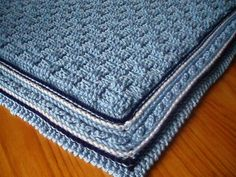 Babies blanket in a basket weave pattern with a ridgedd and cabled border. In DK yarn, this blanket is very warm and cosy. It is made using DK