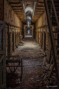 A corridor lined with inmate cells in the Eastern State Penitentiary in Philadelphia, PA. Abandoned Prisons, Old Abandoned Buildings, Abandoned Mansions, Old Buildings, Abandoned Places, Haunted Asylums, Haunted Places, Haunted Prison, Eastern State Penitentiary