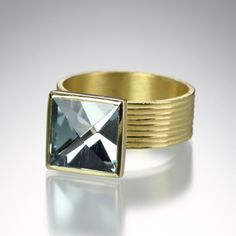 An 18K yellow gold 6.5mm flat fluted band with a 10mm square, context cut,  aquamarine, 3.42cttw. Size 6.5.